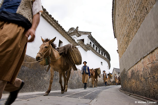 A horse caravan passing the Bending Building in the 600-year-old town of Heshun in southwest Yunnan, China.